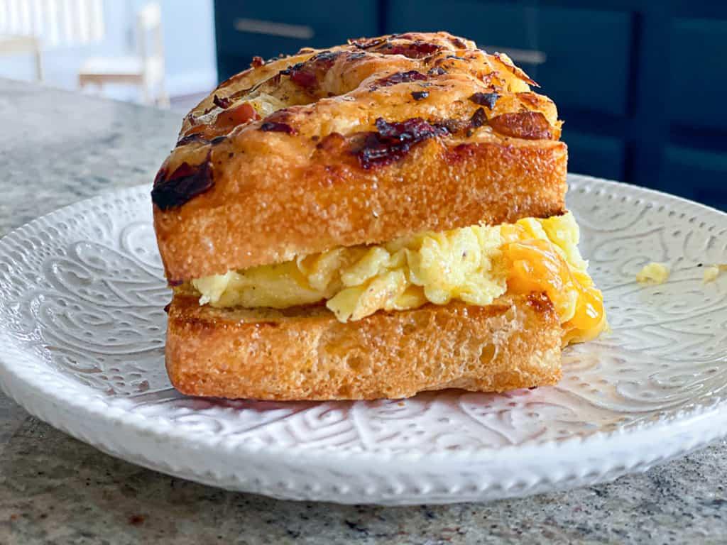 Side shot of breakfast sandwich on frozen then thawed focaccia bread.