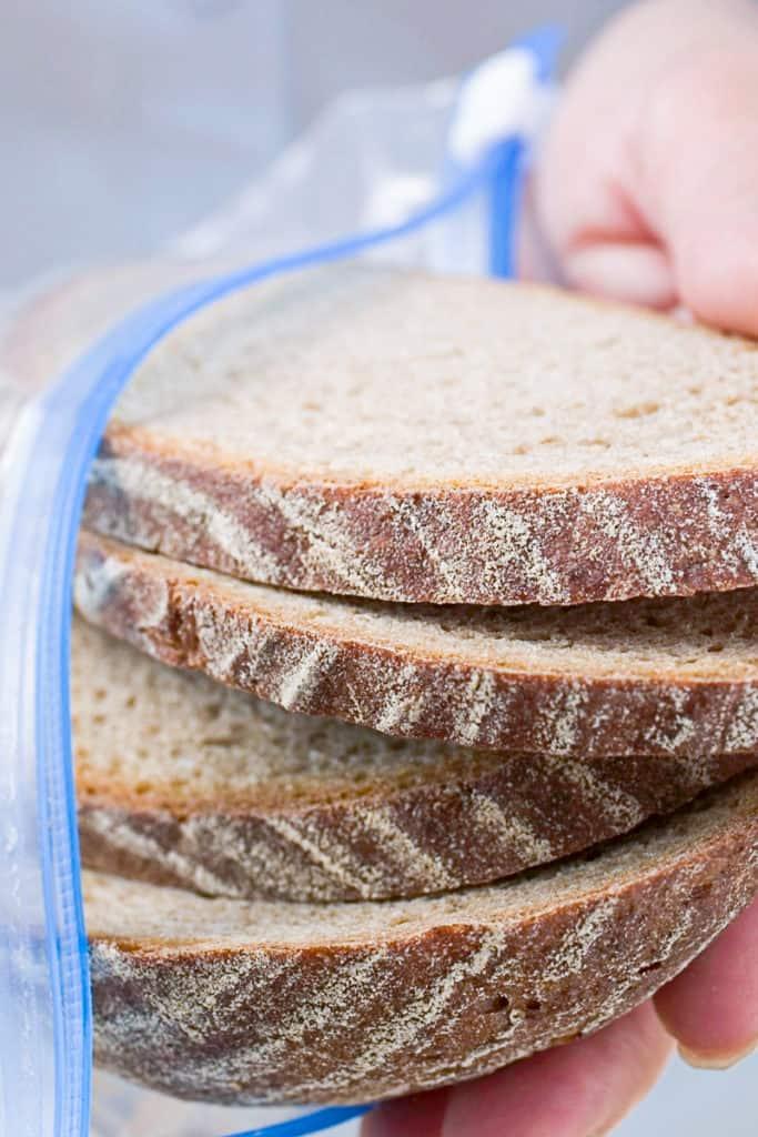 Side shot of hands freezing a loaf of bread in a ziplock plastic bag.