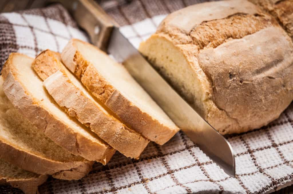 Side shot of knife slicing homemade bread