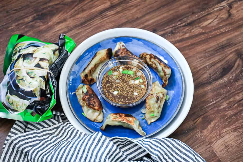 Top down shot of Trader Joe's Thai Vegetable Gyoza package with cooked gyoza dumplings and dipping sauce.