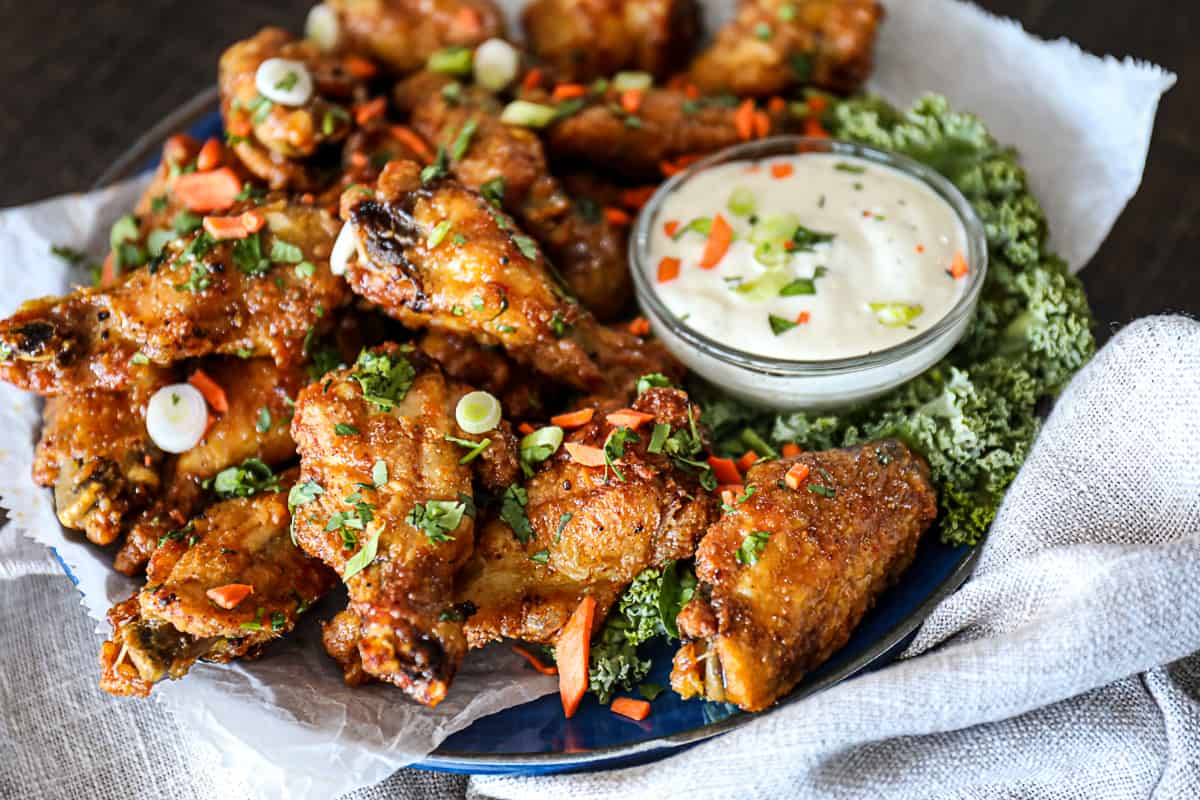 Side shot of chicken wings party appetizer with dipping sauce.