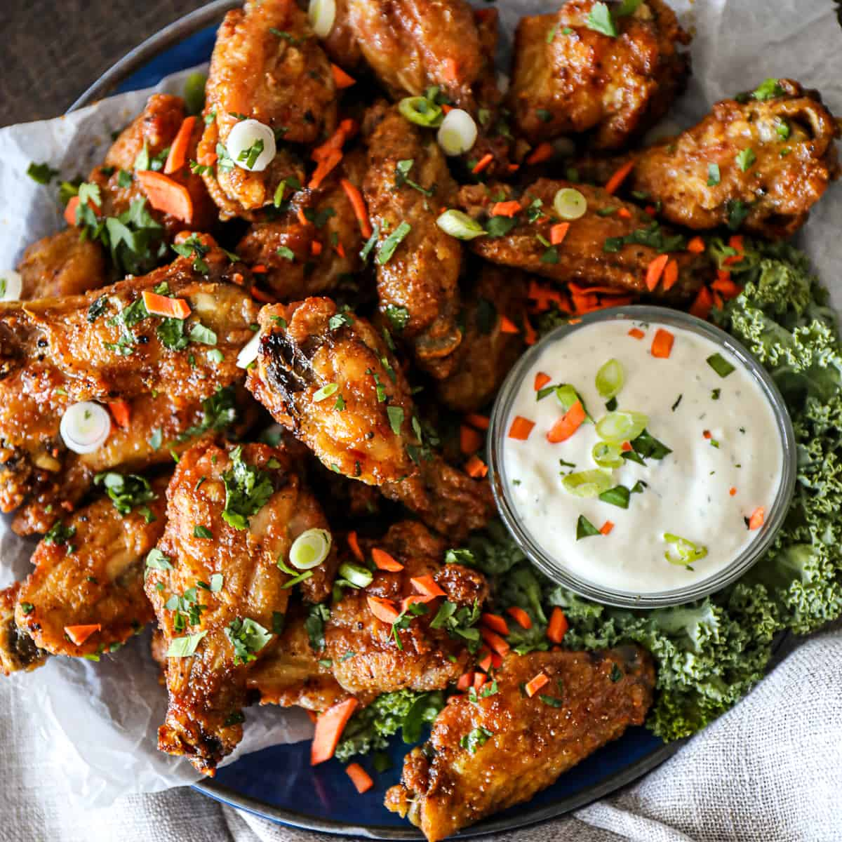 Top down shot of crispy baked chicken wings with blue cheese dressing on a party platter.