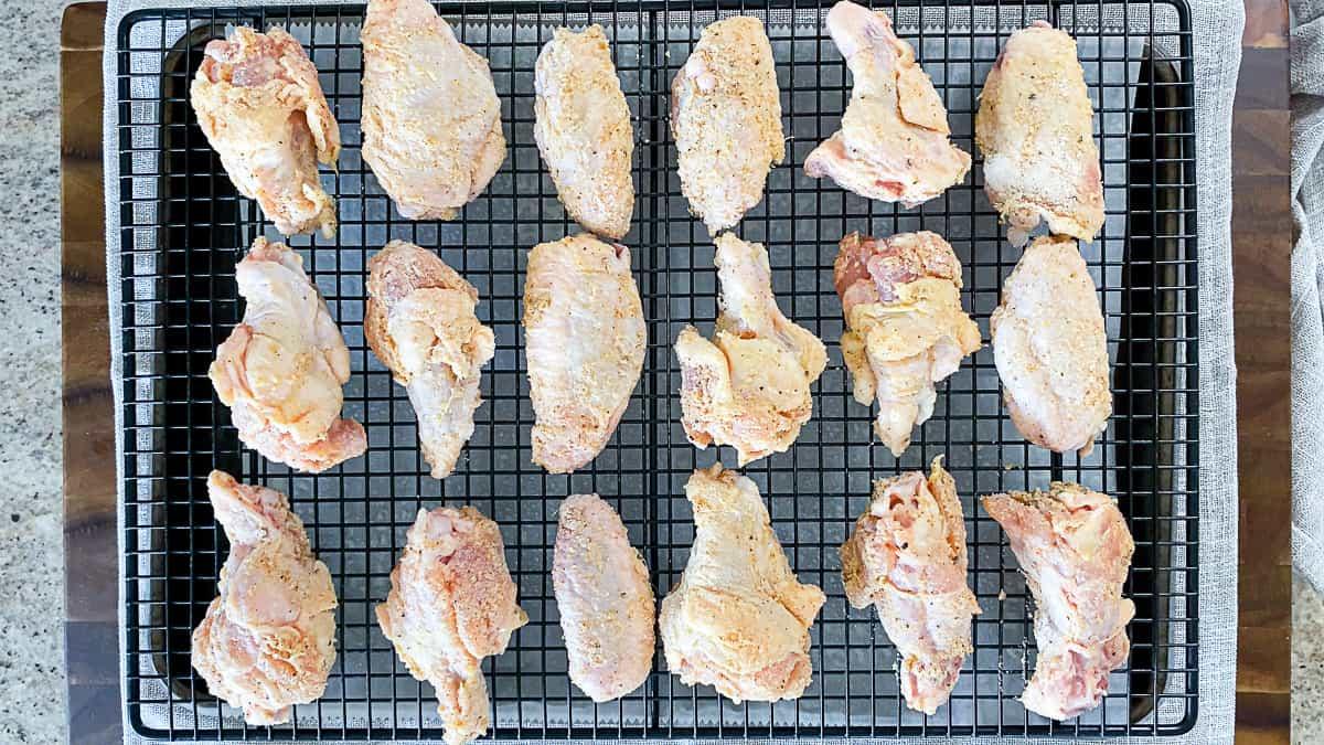 Top down shot of seasoned chicken wings on a wire rack on a baking sheet.