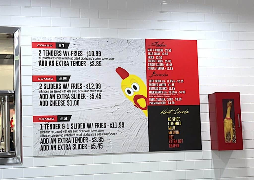 Dave's Hot Chicken Menu With Prices hanging on the wall of the restaurant.