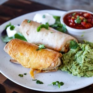 Side shot of cooked Frozen Burrito In Air Fryer to golden brown with sides on a plate.