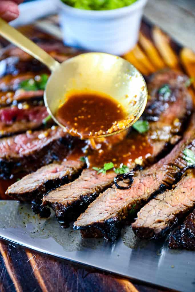 Side shot of a spoon drizzling steak marinade on sliced flank steak.