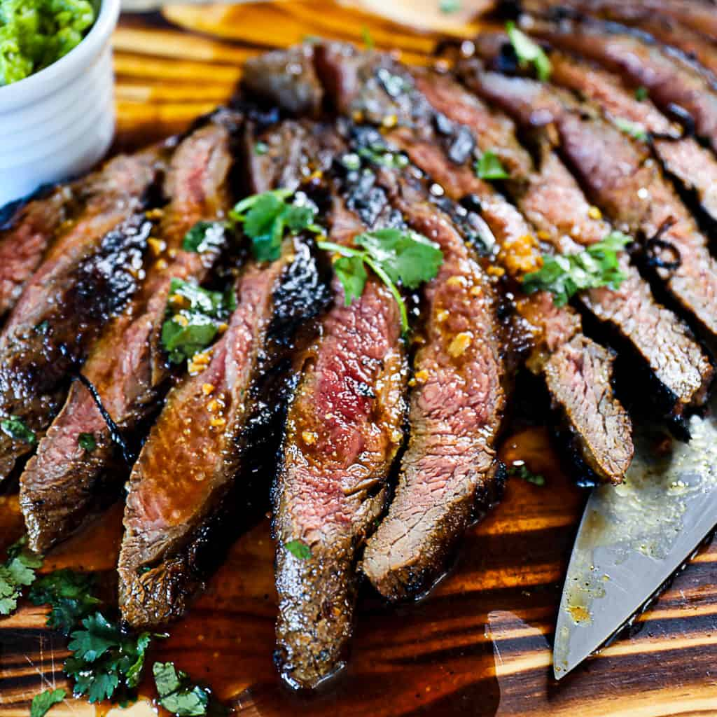Side shot of Flank Steak Marinade on medium rare steak with cilantro and fresh ginger on a cutting board.