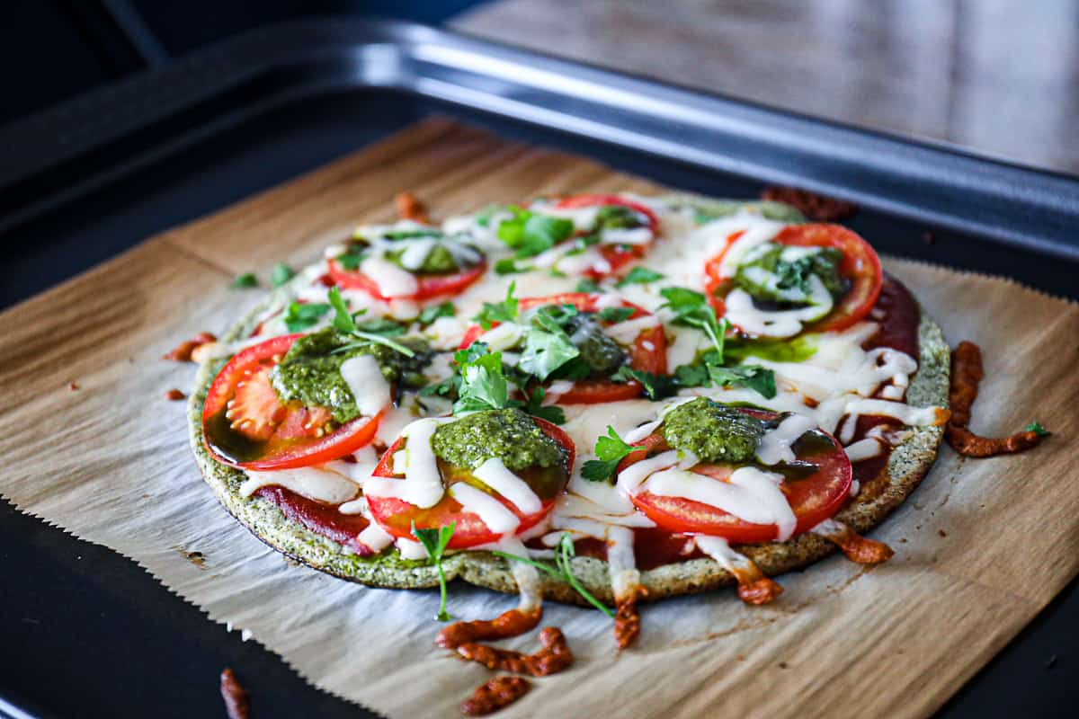 Closeup of melted cheese on tomatoes with pesto on broccoli pizza crust.