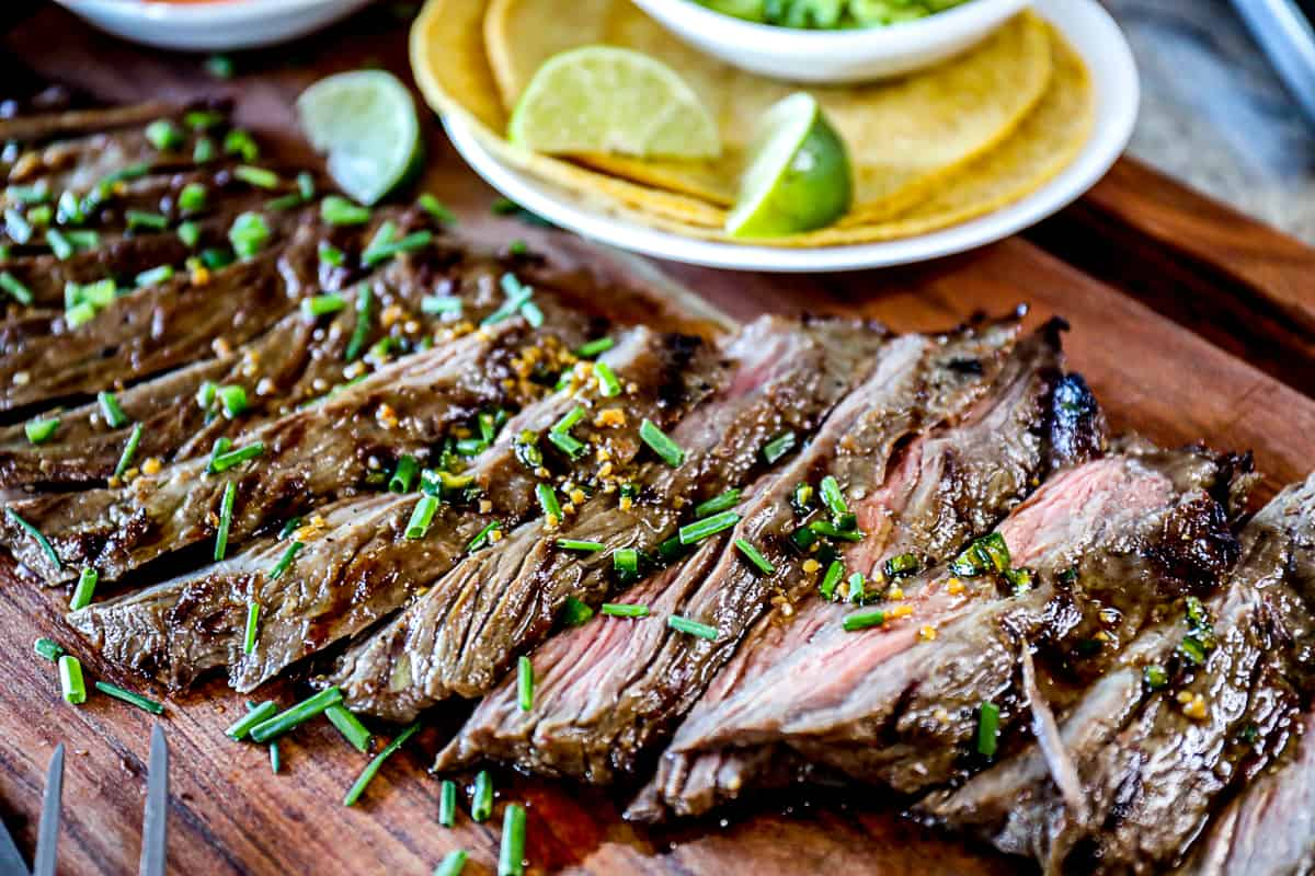 Side shot of platter of skirt steak for tacos with corn taco shells and limes.
