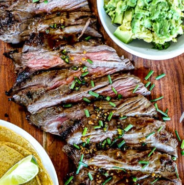 Top down shot of Grilled Skirt Steak Recipe With Marinade and chives and guacamole and tacos.