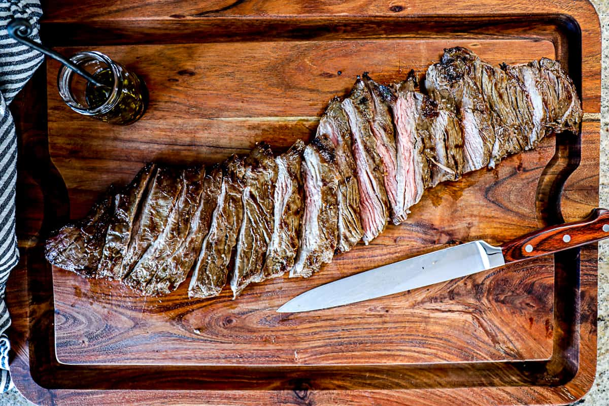 Top down shot of resting steak on a cutting board after grilling with a side of marinade.