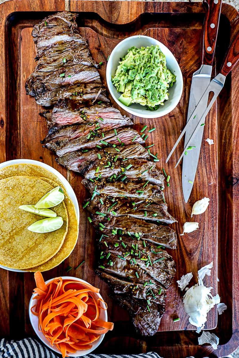 Top down shot of grilled skirt steak recipe on a large party platter cutting board with taco shells, lime, and guacamole.