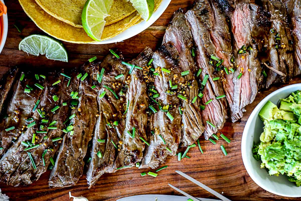 Top down shot of sliced grilled skirt steak with taco ingredients on a serving board.