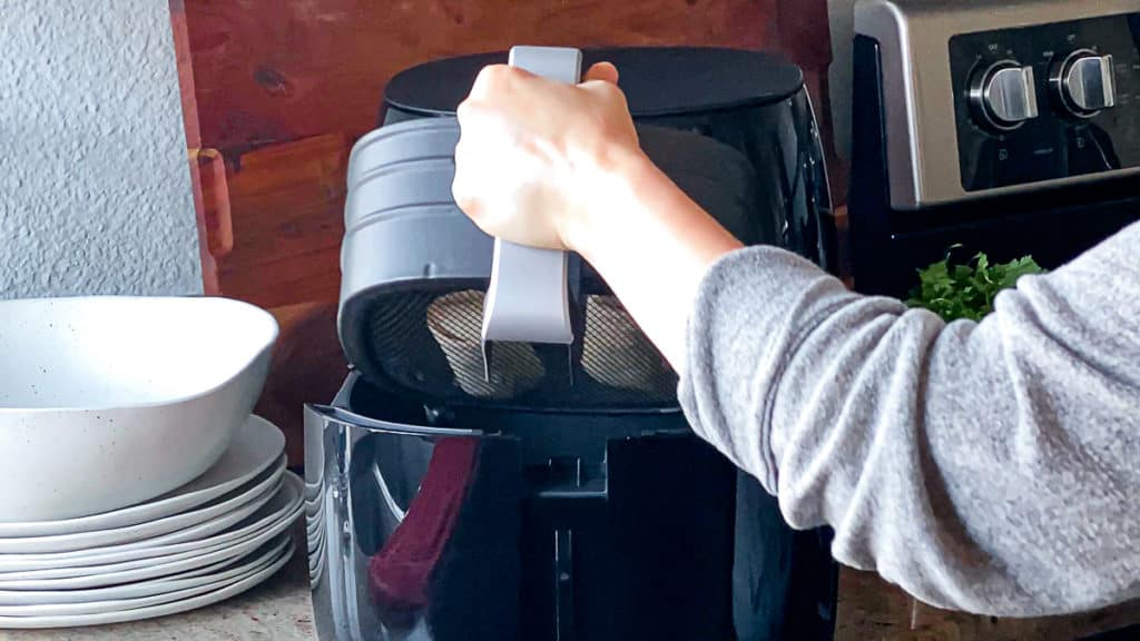 Side shot demonstrating how to add air fryer basket to phillips xl air fryer machine.