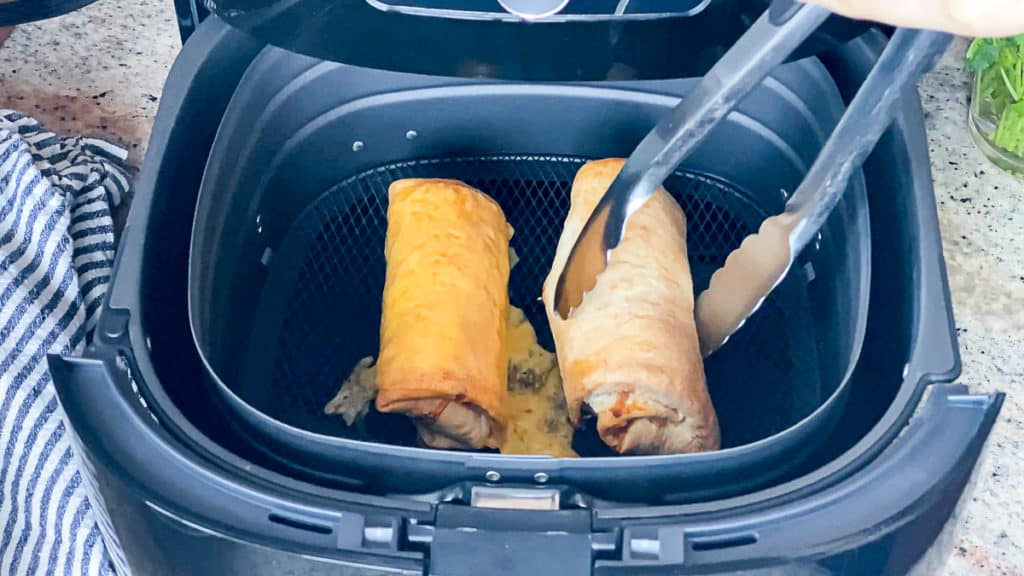 Top down shot demonstrating how to flip air fryer food during cooking process with tongs.
