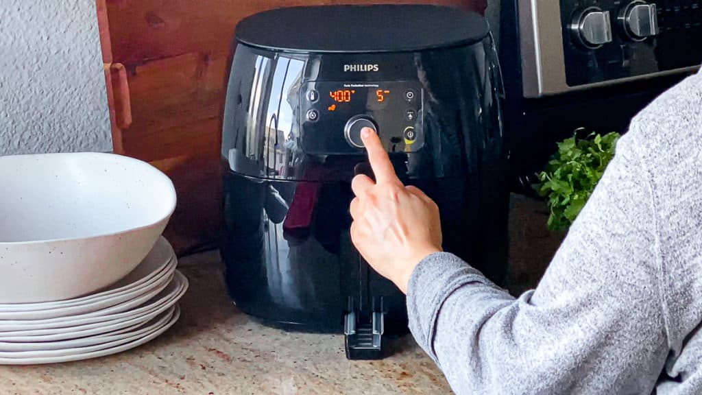 Side shot with hand demonstrating how to turn on air frying function on phillips xl air fryer machine.
