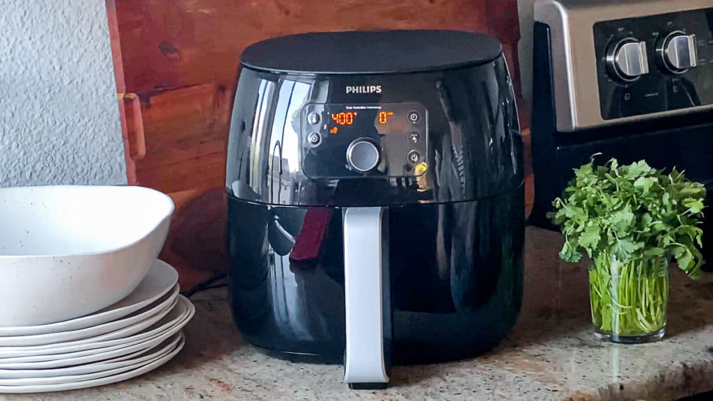 Side shot of phillips air fryer xl machine on a counter with plates and fresh herbs.