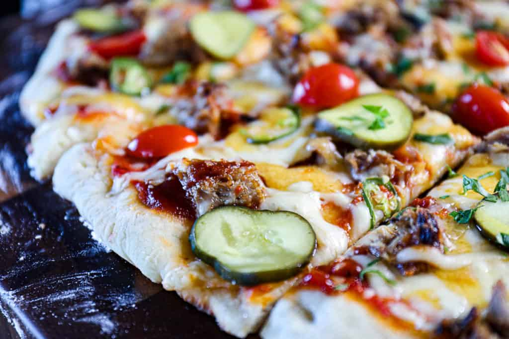 Side shot closeup of pizza with pulled pork, bbq and pickles.