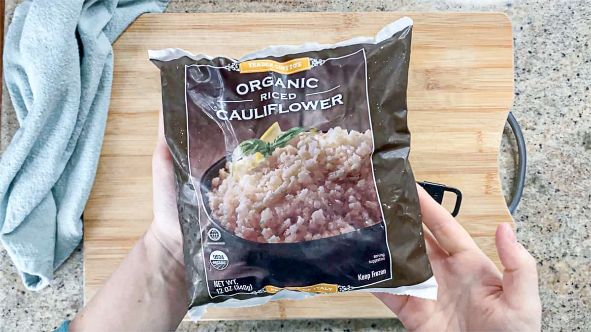 Top down shot of hands holding cauliflower rice from Trader Joe's.
