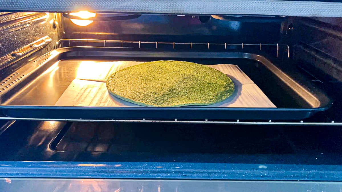 Side shot with open oven door and broccoli crust baking on a sheet tray.