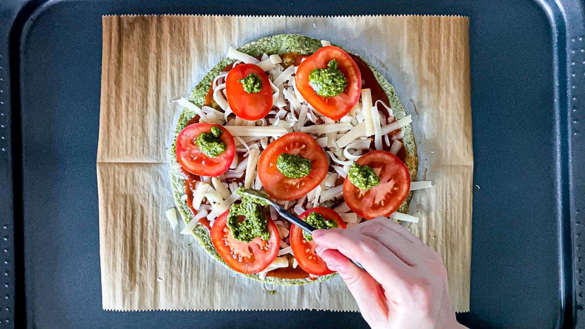 Top down shot of hand adding mozzarella cheese, sliced tomato, and pesto.