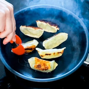 Top down shot demonstrating how to cook Trader Joe's Vegetable Gyoza in a pan.