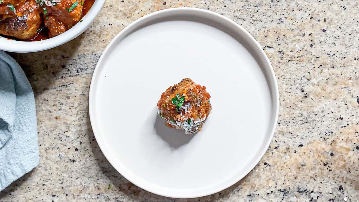 Top shot of meatball with riced cauliflower on a plate with cheese and parsley.