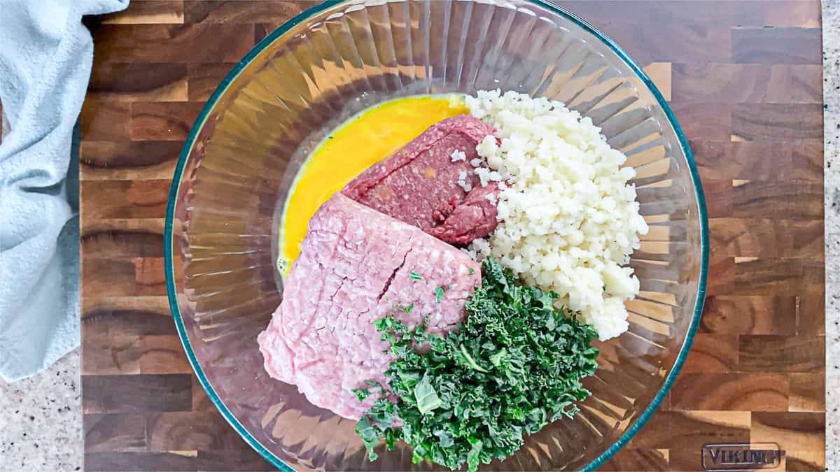 Top down shot of ingredients including ground beef, ground pork, cauliflower, kale and eggs in a large bowl.