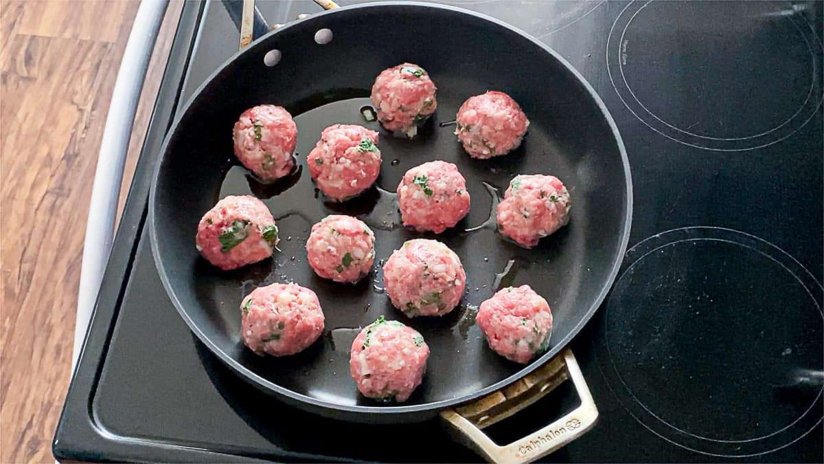 Side shot of homemade keto meatballs searing in a pan.