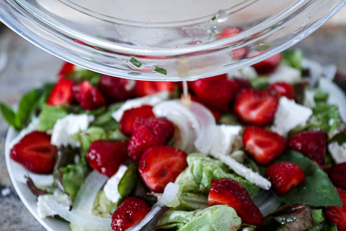Pouring Honey Lemon Basil Dressing on fruit and vegetable salad.