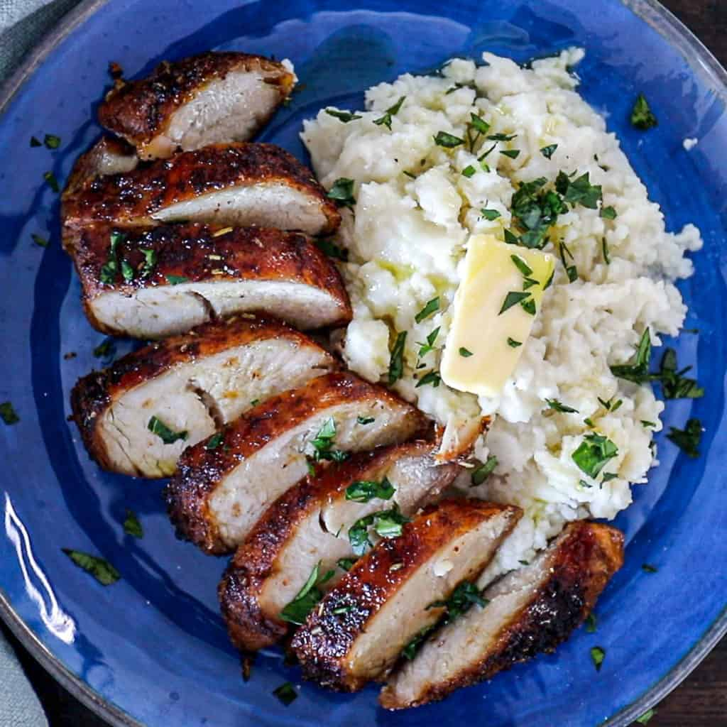 Top down shot of Air Fryer Turkey Breast Recipe with herbs and mashed potatoes on a plate.