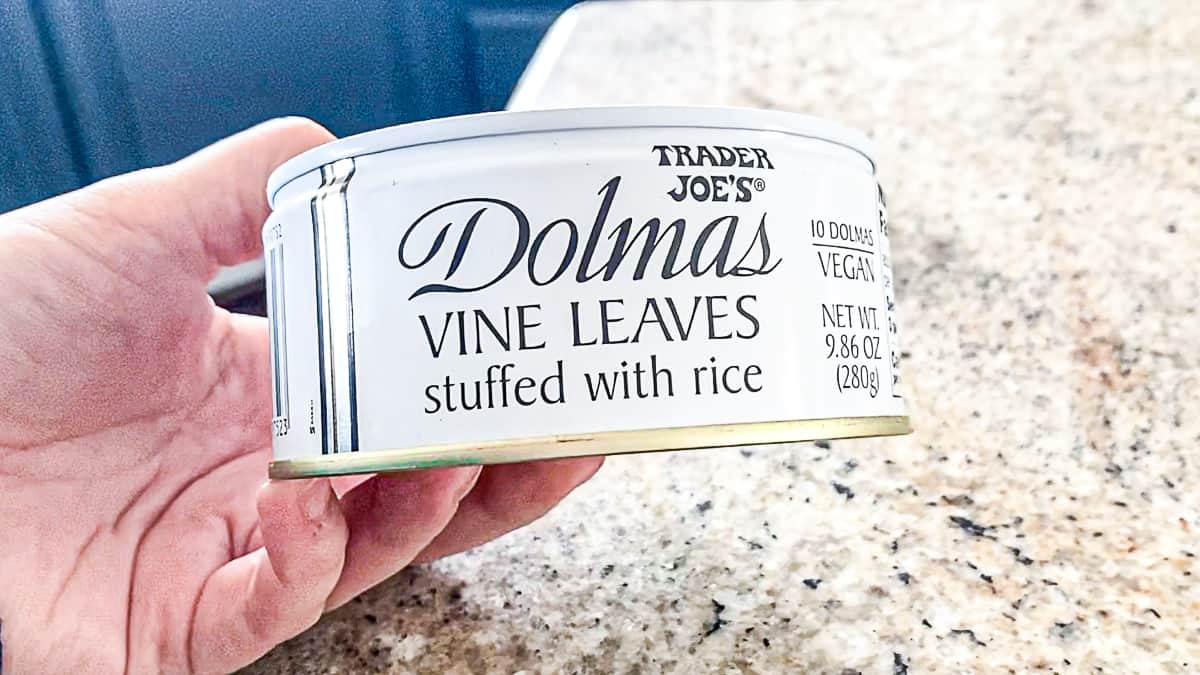 Side shot of hand holding a can of trader joe's dolmas vine leaves stuffed with rice.