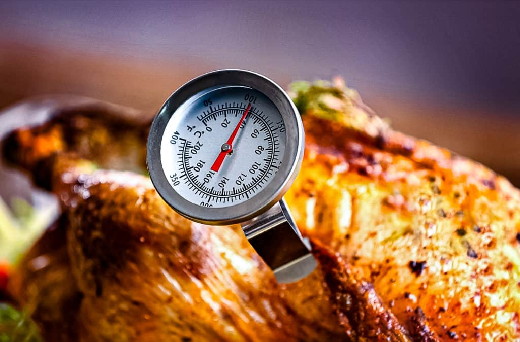 Reading chicken internal temperature with a thermometer.