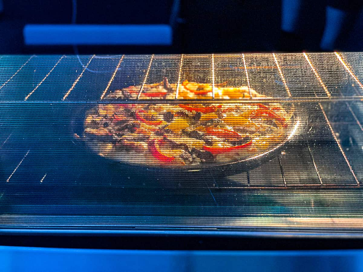 Side shot of convection oven cooking pizza.