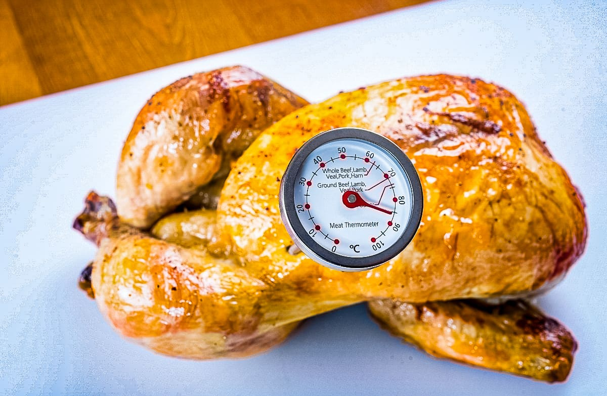 Demonstrating roasted Whole Chicken temperature checking with an internal thermometer stuck in it.