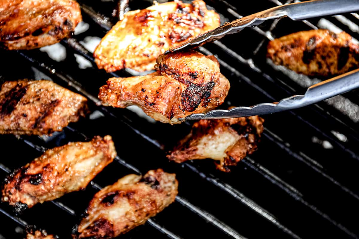 Tong flipping Chicken Wings on the grill.