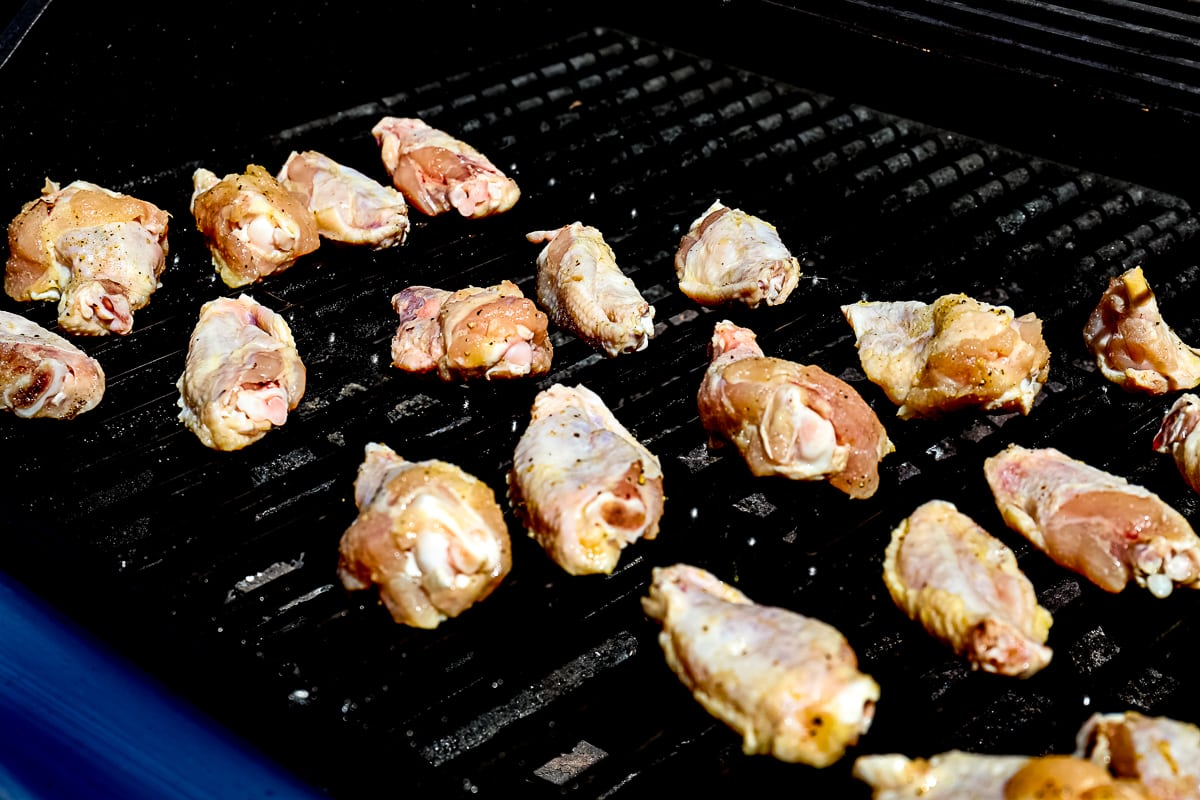 Grilling Chicken Wings on gas grill grates.