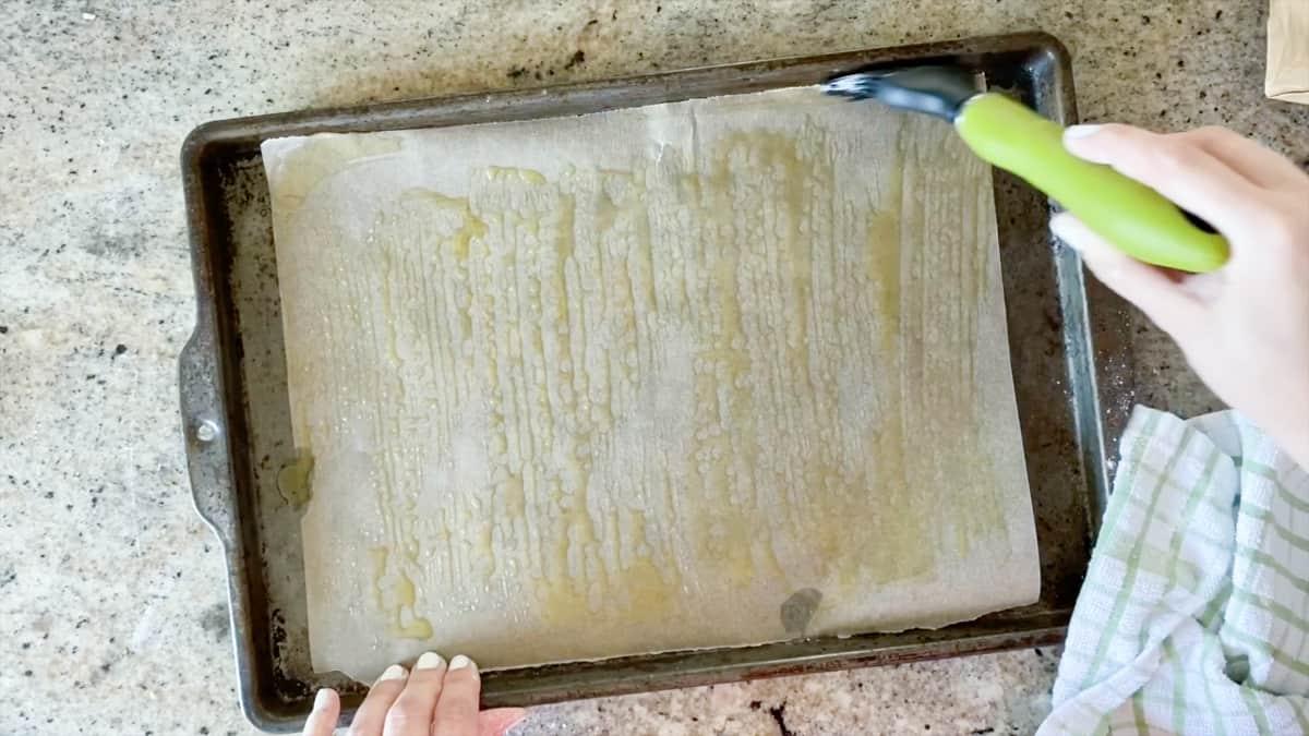 Top down shot of hands brushing olive oil on baking sheet for par baking dough.