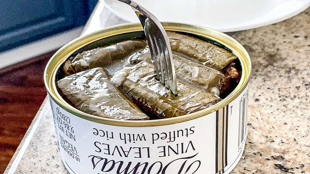 Side shot of photo with fork stabbing stuffed grape leaf in a can from Trader Joe's