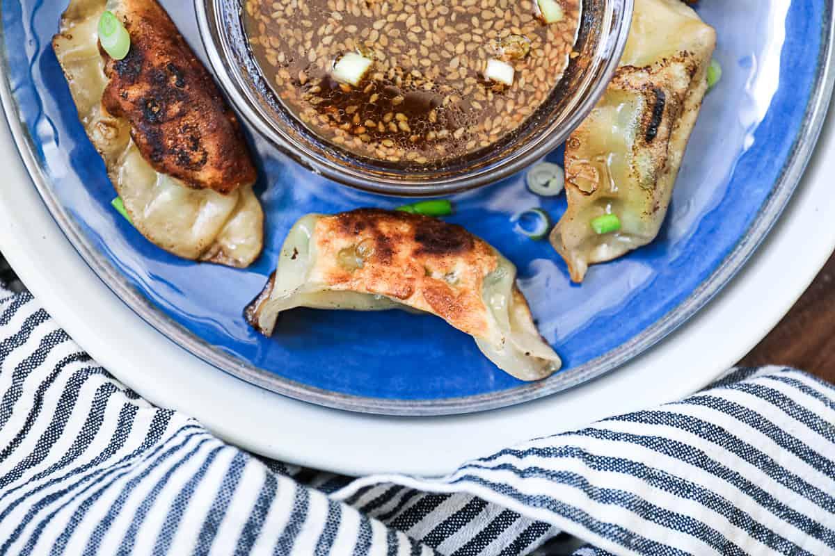 Top down shot of Trader Joe's gyozas and teriyaki sauce on a plate.