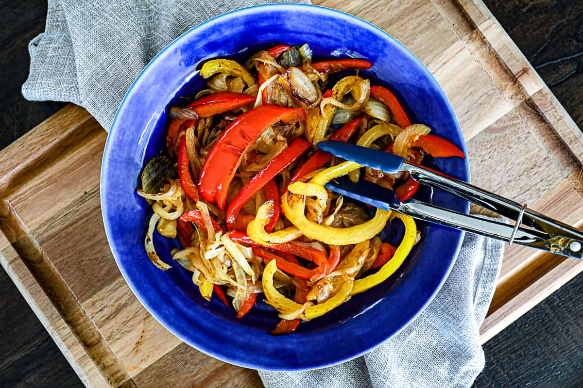 Top down shot of dinner side dish with sauteed onions and peppers on a cutting board.