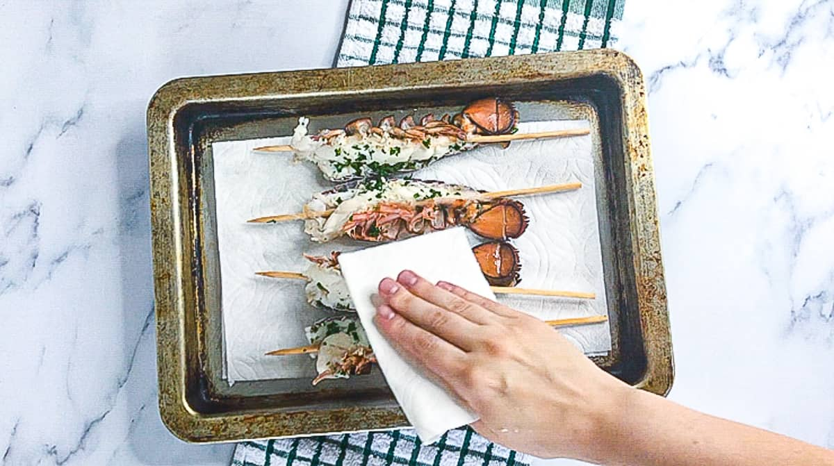 Skewered lobster tails in a pan.