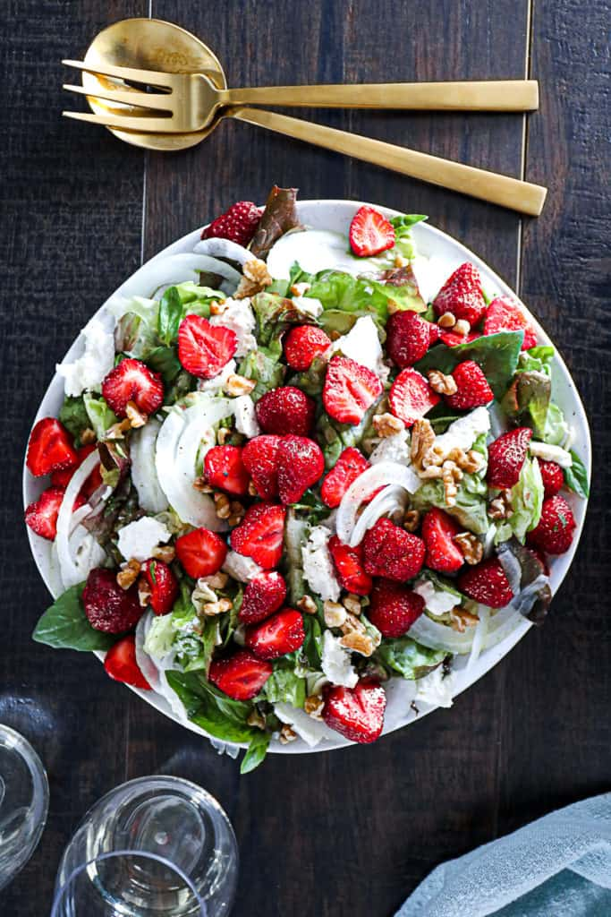 Top down shot of strawberry salad with walnuts and feta cheese on a table with wine and salad spoons.