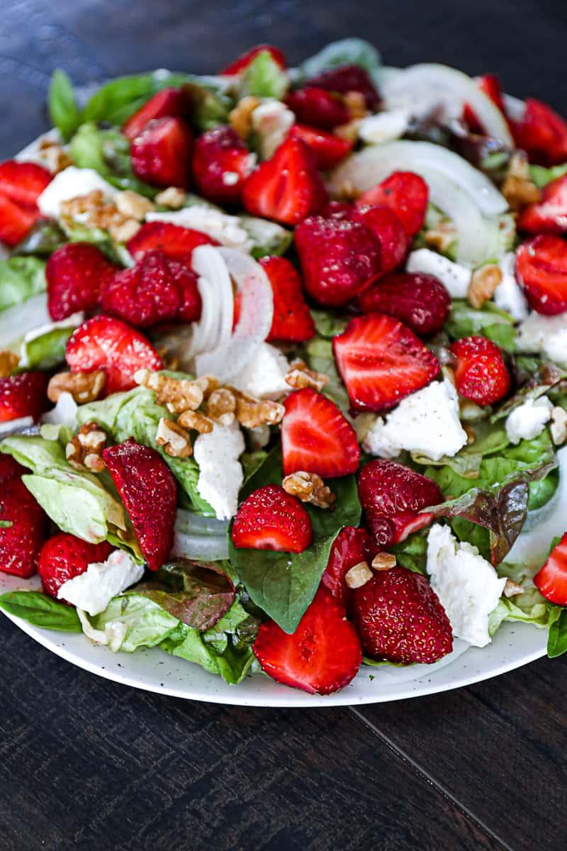 Side shot of strawberry walnut feta salad on a serving party side dish bowl.