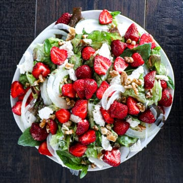 Top down shot of Strawberry Feta Salad With Walnuts and Basil Dressing on a plate.