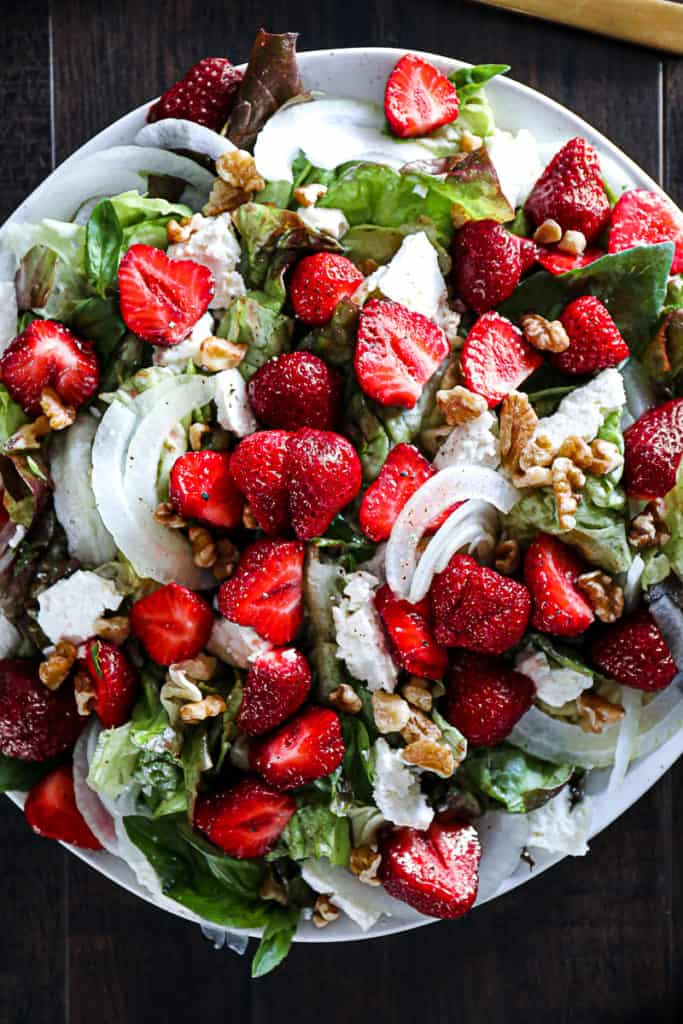 Top down shot of a side dish salad with strawberries, feta cheese, onions, walnuts, and a basil dressing.