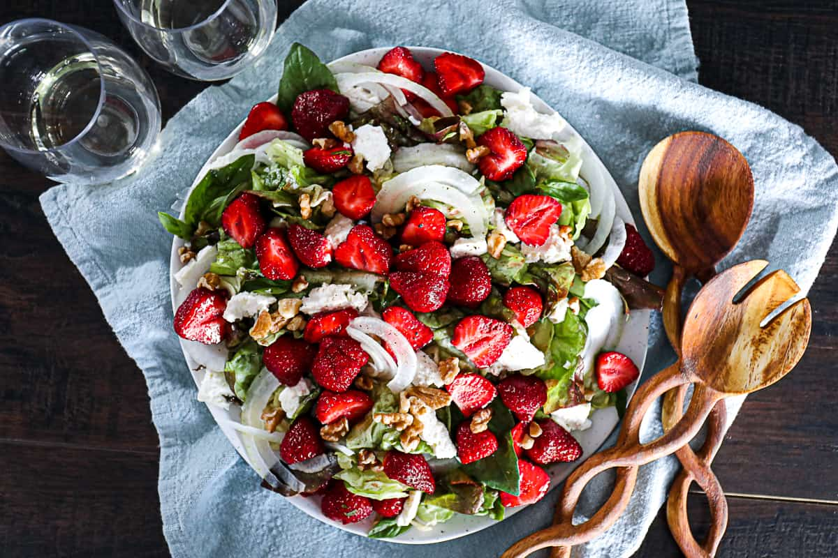 Top down shot serving a large summer lunch salad with strawberries walnuts feta and a side of wine.