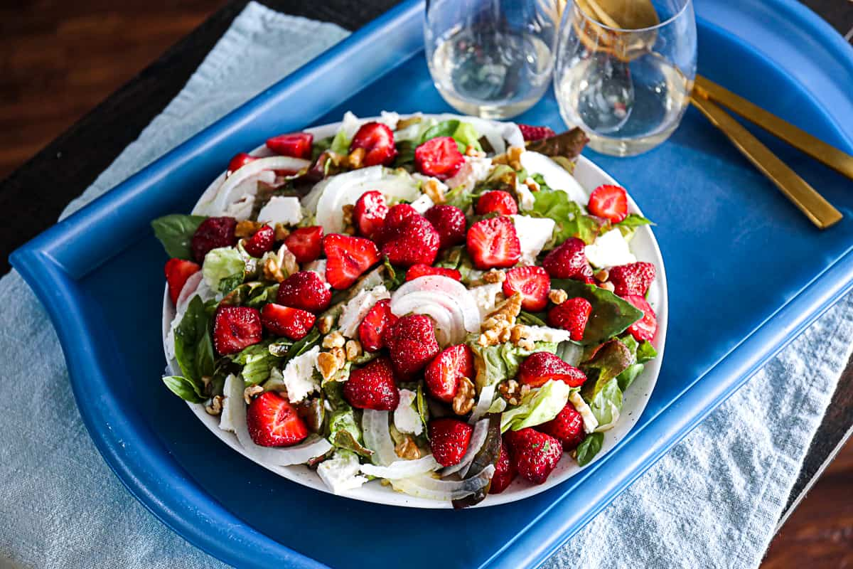 Side shot serving strawberry salad on a tray for a bbq party side dish with white wine.