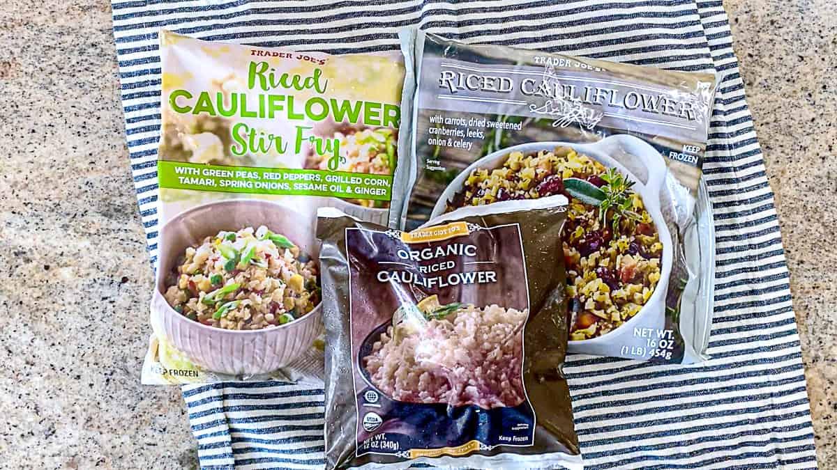 Top down shot of Trader Joe's Cauliflower Rice Products including stir fry cauliflower rice, frozen cauliflower rice, and stuffing cauliflower rice.