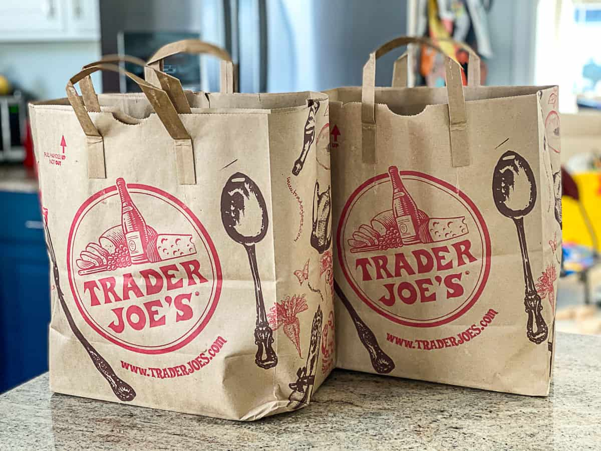 Side shot of two Trader Joe's Haul Shopping Bags On Counter in kitchen.